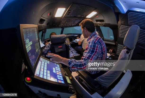 An instructor takes his seat in from of the computer while pilots get ready in TAP A320 medium range flight simulator before the start of a training...