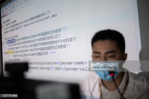 An instructor teaches an online coding class at Tarena International's Zhongguancun campus in Beijing on July 24, 2020. - Some 700 students enrolled...