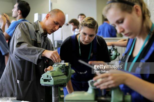 An instructor teaches mechanical engineering trainees the basics of precision filing at the Siemens training center on September 1 2010 in Berlin...