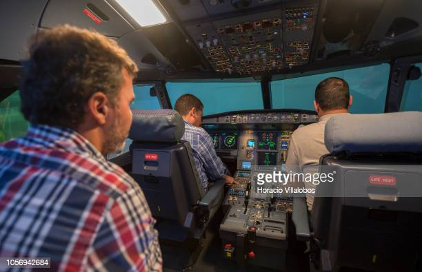 An instructor watches while pilots get ready in TAP A320 medium range flight simulator before the start of a training session at TAP Air Portugal...