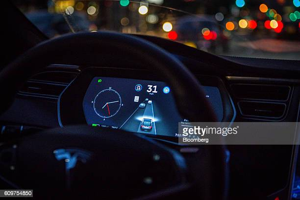 An instrument panel with the Tesla Motors Inc 80 software update illustrates the road ahead using radar technology inside a Model S P90D vehicle in...