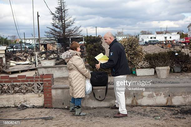 An insurance appraiser speaks with a woman who lost her home in a fire after Superstorm Sandy swept through on October 31 2012 in the Breezy Point...
