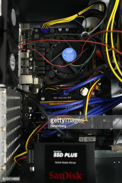 An Intel Corp heat sink and fan for a central processing unit top and a Sandisk Corp solid state drive bottom are seen inside a cryptocurrency...