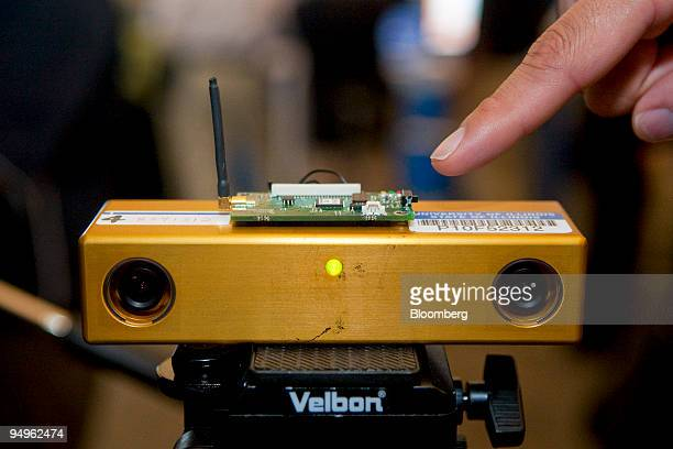 An Intel researcher points to a tripod holding a stereo camera that records 3D video during the annual Research at Intel event at the Computer...