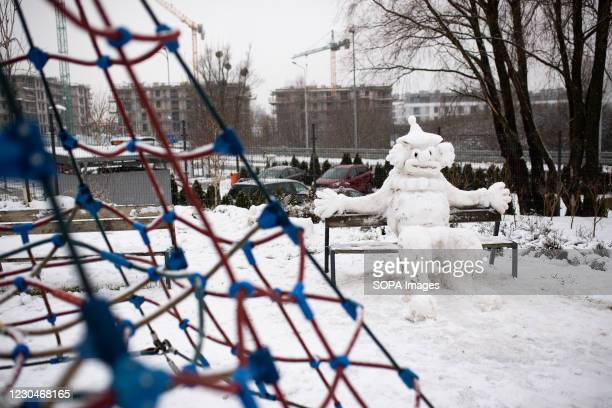 An Interesting snowman sculpture seated at bench inside a playground in Gdansk. The long-awaited snow season has come to Gdansk. During this period...