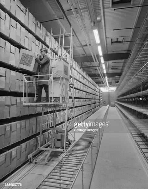 An interior view of the new Pirelli factory, showing shelving stacked with boxes and a man on a mobile platform lifting a box. The Pirelli factory in...