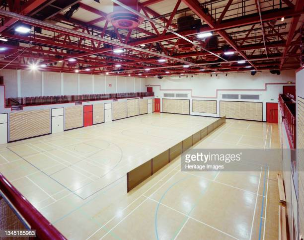 An interior view of the sports hall at 'The Sands' leisure centre in Carlisle, showing sports courts and retractable seating on the far wall. This...