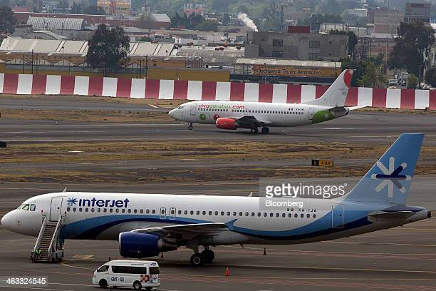 An Interjet airplane sits parked on the tarmac while a Grupo Viva Aerobus SAB airplane prepares to take off at Benito Juarez International Airport in...