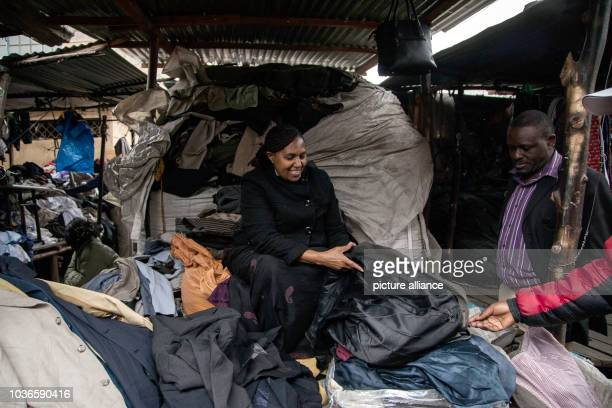 An intermediary arranges clothes at the Gikomba market in Nairobi Kenya 20 July 2016 Thousands of bundles of secondhand clothes are delivered to the...