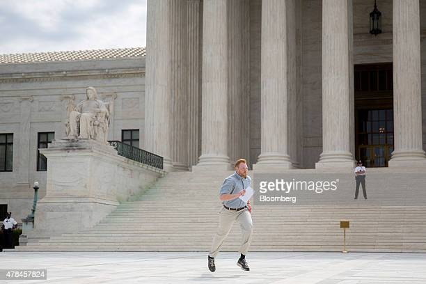 An intern runs the Obamacare tax subsidies opinion to colleagues after the US Supreme Court ruled 63 to save Obamacare tax subsidies outside the...