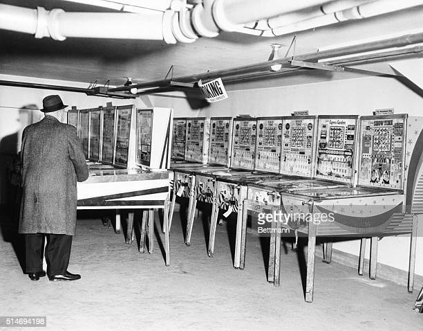 An Internal Revenue Service agent looks over pinball machines seized because they lacked $250 Federal Excise Tax stamps | Location United States...
