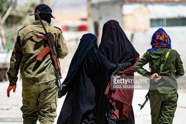 TOPSHOT An internal security patrol escorts women reportedly wives of Islamic State group fighters in the alHol camp in alHasakeh governorate in...
