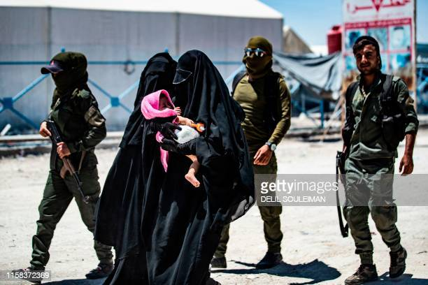 An internal security patrol escorts women reportedly wives of Islamic State group fighters in the alHol camp in alHasakeh governorate in northeastern...
