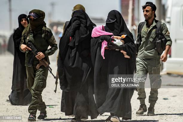 An internal security patrol escorts women, reportedly wives of Islamic State group fighters, in the al-Hol camp in al-Hasakeh governorate in...