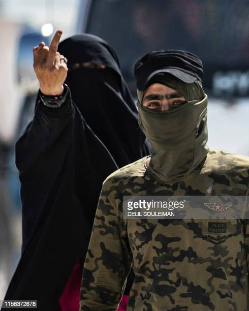 An internal security patrol member escorts a woman giving a middlefinger gesture reportedly a wife of an Islamic State group fighter in the alHol...