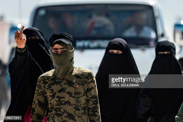 TOPSHOT An internal security patrol member escorts women reportedly wives of Islamic State group fighters in the alHol camp in alHasakeh governorate...