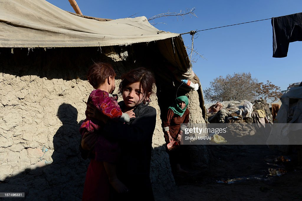 An internally displaced Afghan child holds her brother in a makeshift camp as winter approaches in Kabul on December 4, 2012. The country has nearly half a million displaced people, many living in primitive camps where the cold weather will mean uncertainty for some. AFP PHOTO/SHAH Marai