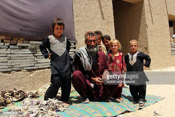 An internally displaced Afghan family poses for a photograph at a temporary home after they fled ongoing clashes between Afghan security forces and...