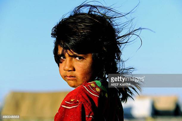 An internally displaced Afghan girl poses for a photograph in front of her tent on the outskirts of Herat on May 12 2014 The number of internally...