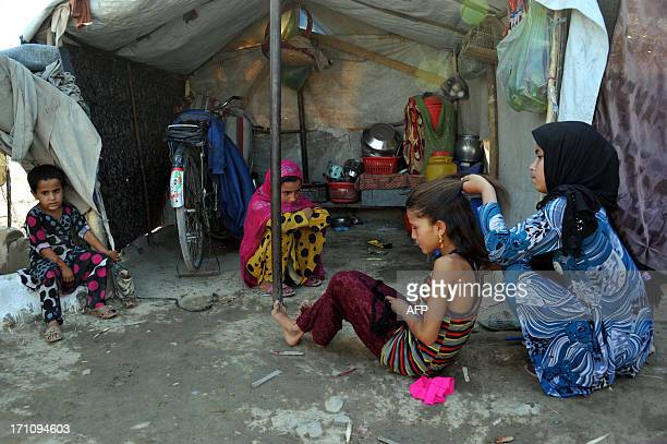 An internally displaced Afghan refugee child sorts out another girl's hair at a refugee camp on the outskrits of Jalalabad on June 21 2013 Scarred by...