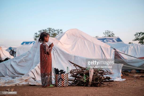 An Internally Displaced child, fleeing from violence in the Metekel zone in Western Ethiopia, stands next to a pile of wood at a camp in Chagni,...