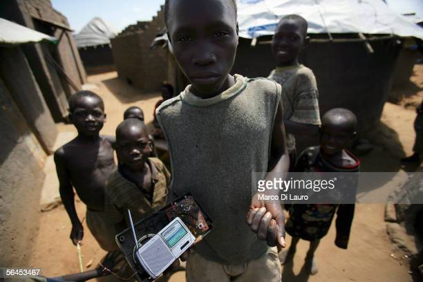 An Internally Displaced child holds a old radio and some food in front of his shelter in the Pabo refugee Camp on December 10 2005 in the outskirt of...