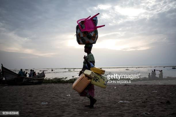 TOPSHOT An internally displaced Congolese women walks with her belongings along the shore line of lake Albert after spending the night out in the...