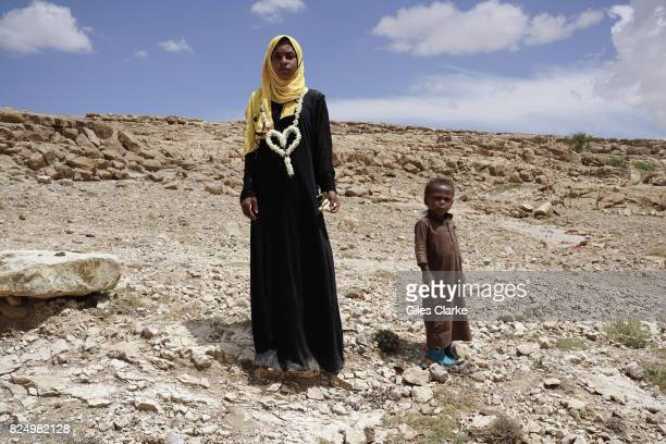 An internally displaced mother and child stand on a rocky landscape in KHAMIR