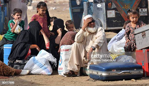 An internally displaced Pakistani family sits with their belongings as they wait for transport at a bus terminal in Karachi to return their home to...