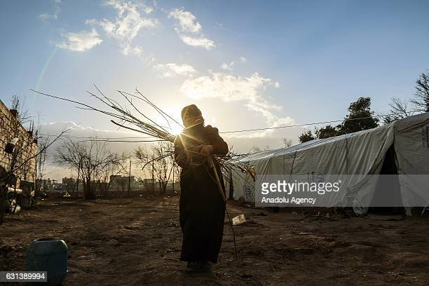 An Internally Displaced Syrian woman fled from East Ghouta region as Assad Regime violates the ceasefire on ongoing civil war carries a bundle of...