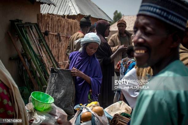 TOPSHOT An internally displaced woman from the Fulani area attacked last week holds a bag as others stand at their temporal house in Kurosin Kajuru...