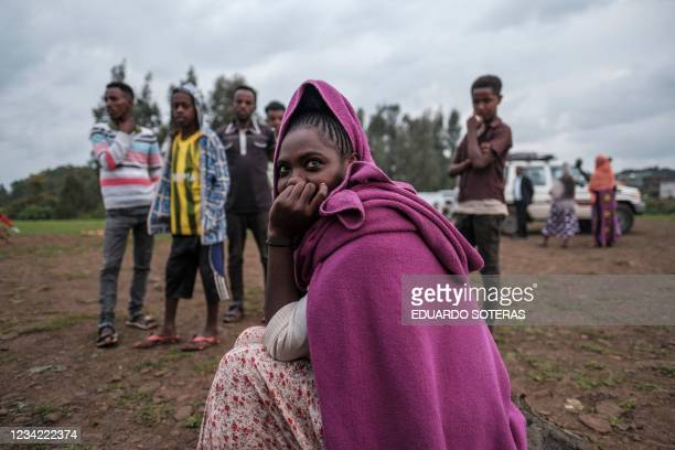 An internally displaced woman sits at the entrance of a camp in the town of Azezo, Ethiopia, on July 12, 2021. The camp hosts Ethiopians as well as...