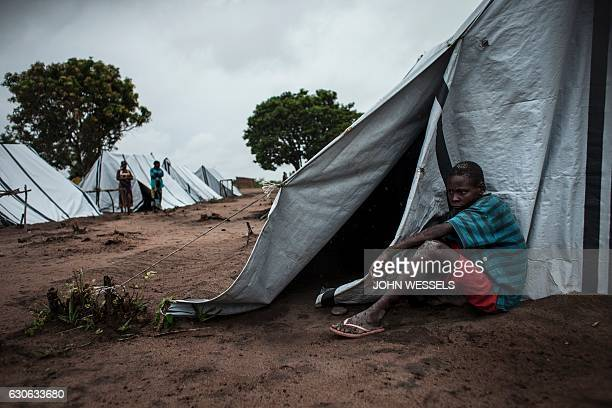 An internally sisplaced Mozambican who fled clashes between the Mozambican Army and Mozambican National Resistance forces sits next to a tent in an...