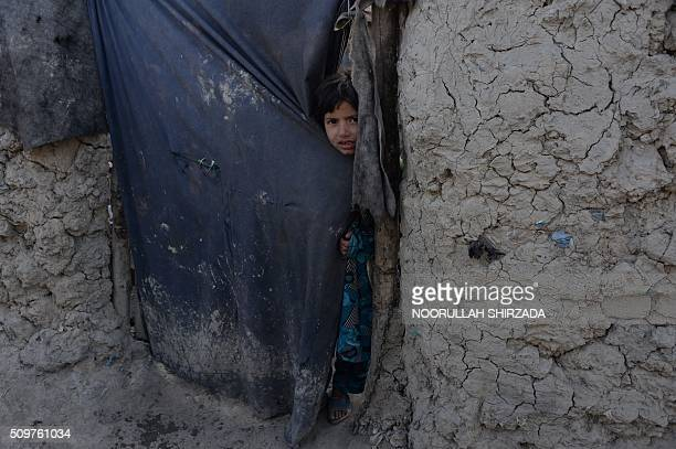 TOPSHOT An internallydisplaced Afghan child looks through the doorway of her temporary home on the outskirts of Kabul on February 12 2016 As winter...