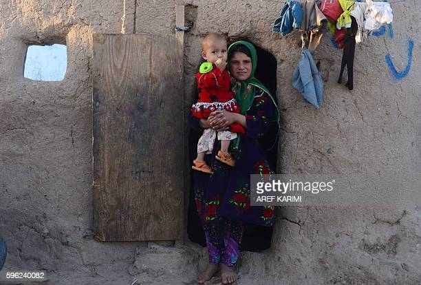 An internallydisplaced Afghan girl holds a child as she stands outside her temporary house on the outskirts of Herat on August 26 2016 / AFP / AREF...