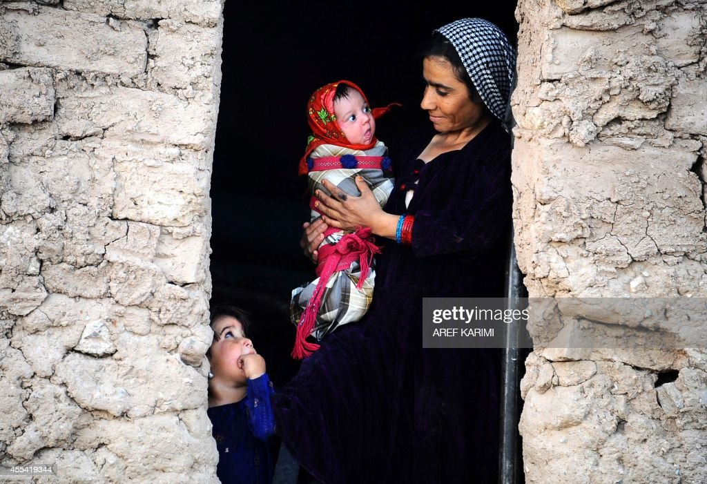 An internally-displaced Afghan resident holds her child as she stands in the doorway of her temporary shelter on the outskirts of Herat province on September 13, 2014. The number of internally displaced people (IDPs) in the country is currently estimated at some 600,000 and this figure may rise further in 2014, according to the UNHCR Global Appeal 2014-2015.