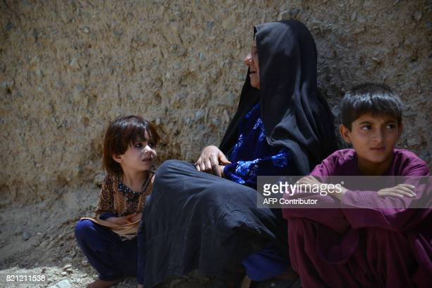 An internallydisplaced Afghan woman and children who left their homes following a masskidnapping by suspected militants look on after arriving from...