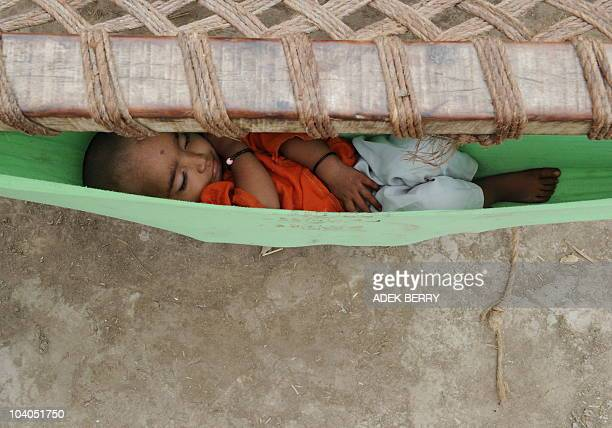 An internally-displaced Pakistani infant naps in a makeshift hammock as people celebrate Eid Al-Fitr at a camp in Sukkur on September 11, 2010....