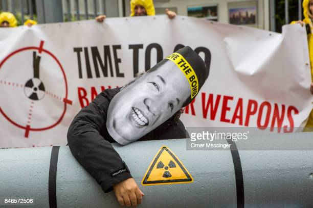 An International campaign to abolish Nuclear Weapons activist wearing a mask with an image of North Korean leader Kim JongUn is posing next to a...