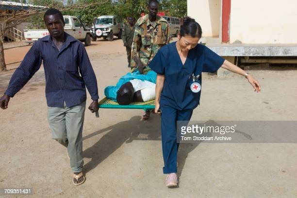 An International Committee of the Red Cross member of the Field Surgical Team helps to carry a patient to a ward after his emergency operation at...