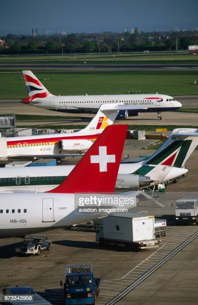 an international mix of tailfins of Swiss International Airlines Airbus A321200 Alitalia and Iberia McDonnell Douglas MD80s with a British Airways GB...