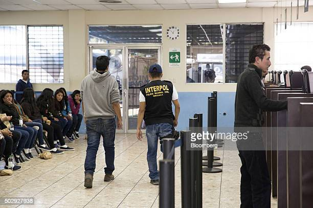 An Interpol agent escorts a deported migrant wanted by authorities for the murder of a woman in the processing center at an Air Force base in...