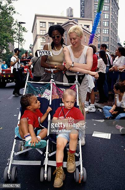 An interracial lesbian couple march in the Gay Pride parade with their two children One of the children holds a 'dyke' sign