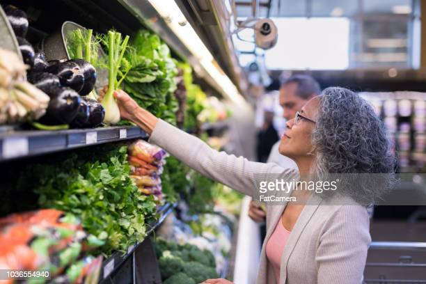 an interracial senior couple goes grocery shopping together - healthy eating stock pictures, royalty-free photos & images