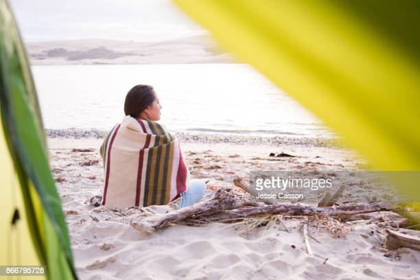 An intrepid female traveller sits alone on a beautiful beach in the evening light - shot taken from inside her tent