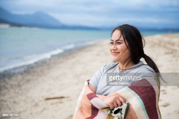 An intrepid female traveller stands on beach wrapped in a shawl looking out to sea