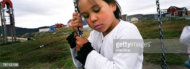 An inuit girl sits on a swing in the village of Ilimanaq august 27 Greenland Even though the disappearing ice cap could lead to higher sea levels all...