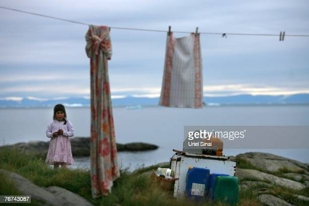 An inuit girl stands at her back yard August 27in the village of Ilimanaq Greenland Even though the disappearing ice cap could lead to higher sea...
