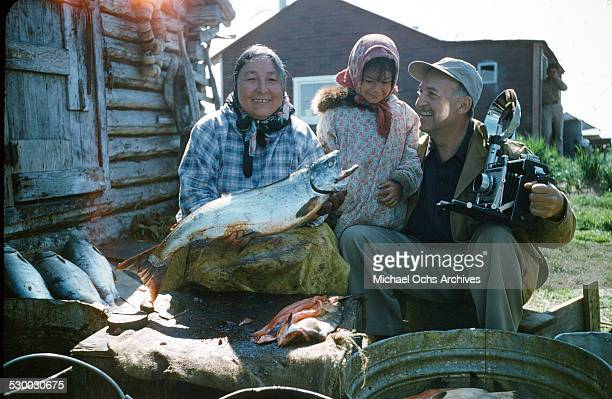 An Inuit women and girl pose with a salmon and photographer in Unalakeet Alaska