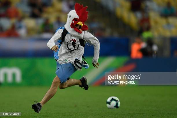 An invader runs on the field during the Copa America football tournament group match between Chile and Uruguay at Maracana Stadium in Rio de Janeiro,...